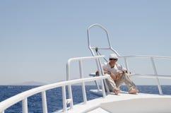 戴一个盖帽和眼镜在游艇的明亮的衣裳的一个人 库存照片