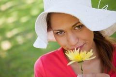 戴一个空白帽子的妇女,当嗅到一朵黄色花时 免版税库存图片