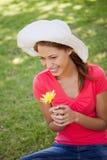 戴一个空白帽子的妇女,当拿着一朵黄色花时 库存照片