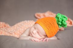 戴一个被编织的红萝卜或南瓜帽子的新出生的婴孩 免版税图库摄影