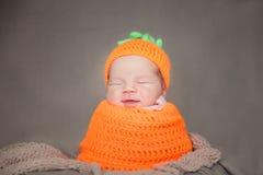 戴一个被编织的红萝卜或南瓜帽子的新出生的婴孩 库存图片
