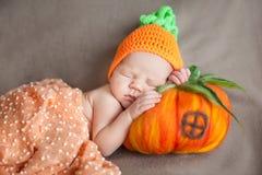 戴一个被编织的红萝卜或南瓜帽子的新出生的婴孩 库存照片