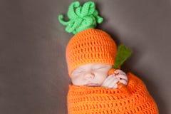 戴一个被编织的红萝卜或南瓜帽子的新出生的婴孩 免版税库存图片