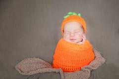 戴一个被编织的红萝卜或南瓜帽子的新出生的婴孩 免版税库存照片