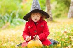 戴万圣夜巫婆帽子的小女孩和温暖红色外套,获得乐趣在公园,秋天天 免版税库存图片