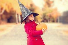戴万圣夜巫婆帽子的小女孩和温暖红色外套,获得乐趣在秋天天 免版税库存图片