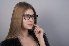 戴今后看的眼镜的年轻美女站立在灰色背景前面和,很多干净的空间 免版税图库摄影