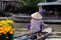 戴传统越南帽子的无法认出的妇女,充分荡桨在小船花准备泰特,湄公河三角洲,越南 库存图片