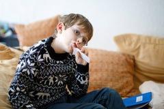戴做家庭作业的眼镜的疲乏的小孩男孩在早晨在学校前在家开始 少许了解的子项 免版税库存照片