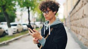 戴卷发和眼镜的少妇与朋友网上身分谈话户外并且使用智能手机和 股票视频