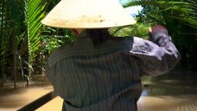 戴叶子帽子和用浆划一个传统小船或独木舟在湄公河三角洲的越南妇女,越南 股票视频