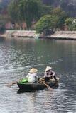 戴圆锥形帽子的划艇妇女参加和荡桨有桨的一条小船在河在背景中在的Trang洞穴 图库摄影