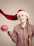戴圣诞老人帮手帽子的愉快的妇女 免版税库存照片