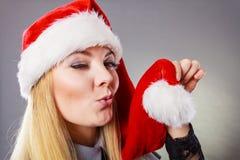 戴圣诞老人帮手帽子的愉快的妇女 免版税库存图片