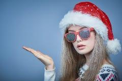 戴圣诞老人帽子和太阳镜的冻女孩显示拷贝空间 免版税图库摄影