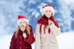 戴圣诞老人帽子的两个可爱的妹食用巨大的镶边圣诞节棒棒糖在美好的冬日 图库摄影
