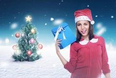 戴圣诞老人帽子的亚裔妇女拿着礼物 库存图片