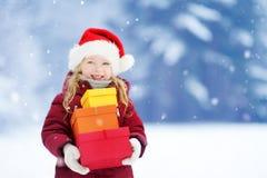 戴圣诞老人帽子的可爱的小女孩拿着堆圣诞节礼物在美好的冬日 免版税库存图片