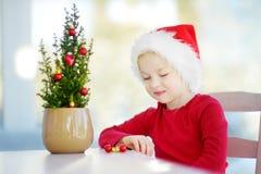 戴圣诞老人帽子的可爱的小女孩装饰在一个罐的小圣诞树在圣诞节早晨 库存图片