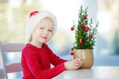 戴圣诞老人帽子的可爱的小女孩装饰在一个罐的小圣诞树在圣诞节早晨 免版税图库摄影