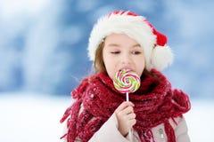 戴圣诞老人帽子的可爱的小女孩食用巨大的镶边圣诞节棒棒糖在美好的冬日 免版税库存图片