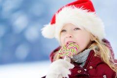 戴圣诞老人帽子的可爱的小女孩食用巨大的镶边圣诞节棒棒糖在美好的冬日 免版税库存照片
