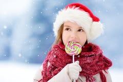 戴圣诞老人帽子的可爱的小女孩食用巨大的镶边圣诞节棒棒糖在美好的冬日 库存图片