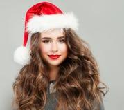 戴圣诞老人帽子的圣诞节妇女 逗人喜爱的少妇模型 免版税图库摄影