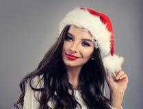 戴圣诞老人帽子的圣诞节式样妇女 库存图片