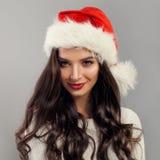 戴圣诞老人帽子的圣诞节式样妇女 免版税库存图片