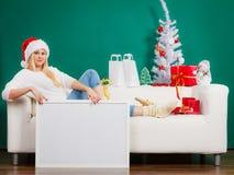 戴圣诞老人帽子的妇女放松在沙发 免版税库存图片