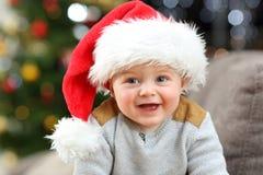 戴圣诞老人帽子的婴孩在家摆在圣诞节 免版税库存照片