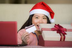 戴圣诞老人帽子的年轻美丽和愉快的亚裔中国妇女拿着信用卡和圣诞礼物箱子使用膝上型计算机估计 库存照片