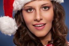 戴圣诞老人帽子的微笑的妇女 库存照片