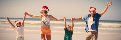 戴圣诞老人帽子的快乐的家庭,当跳跃在海滩时 免版税库存图片