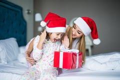 戴圣诞老人帽子的愉快的家庭坐床 母亲给并且使儿童圣诞老人礼物和有乐趣惊奇在圣诞节时间 图库摄影