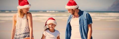戴圣诞老人帽子的愉快的家庭,当站立在海滩时 图库摄影