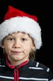 戴圣诞老人帽子的愉快的男孩 库存照片