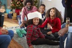 戴圣诞老人帽子的男孩画象作为多一代家庭一起在家庆祝圣诞节 免版税库存图片
