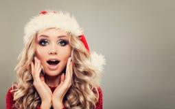 戴圣诞老人帽子的美丽的圣诞节妇女 免版税库存照片