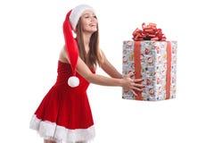 戴圣诞节礼服和帽子的愉快的女孩拿着一个礼物盒用被伸出的手 查出 免版税图库摄影