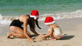 戴在海滩的孩子和母亲一个圣诞老人项目帽子 股票视频