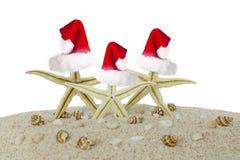 戴在演播室的三个海星圣诞老人帽子 图库摄影