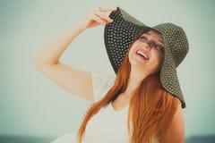 戴大黑太阳帽子的愉快的红头发人妇女 免版税库存图片