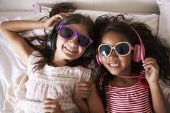 戴太阳镜和听到音乐的两个女孩画象  免版税库存图片