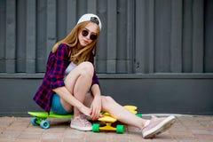 戴太阳镜的一个俏丽的白肤金发的女孩、方格的衬衣和牛仔布短裤坐明亮的logboards在前面 图库摄影