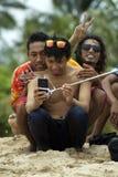 戴太阳镜的年轻亚裔人采取与朋友的selfie 免版税库存照片