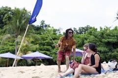 戴太阳镜的年轻人采取与少妇的selfie坐海滩 库存照片