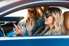 戴太阳镜的愉快的金发碧眼的女人照片,当驾驶在汽车时 库存图片