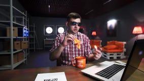 戴太阳镜的逗人喜爱的有胡子的人投入火被折叠的橙色origami起重机 股票视频